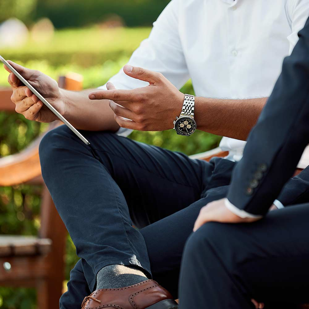 man wearing watch and pointing at ipad with man in suit beside him