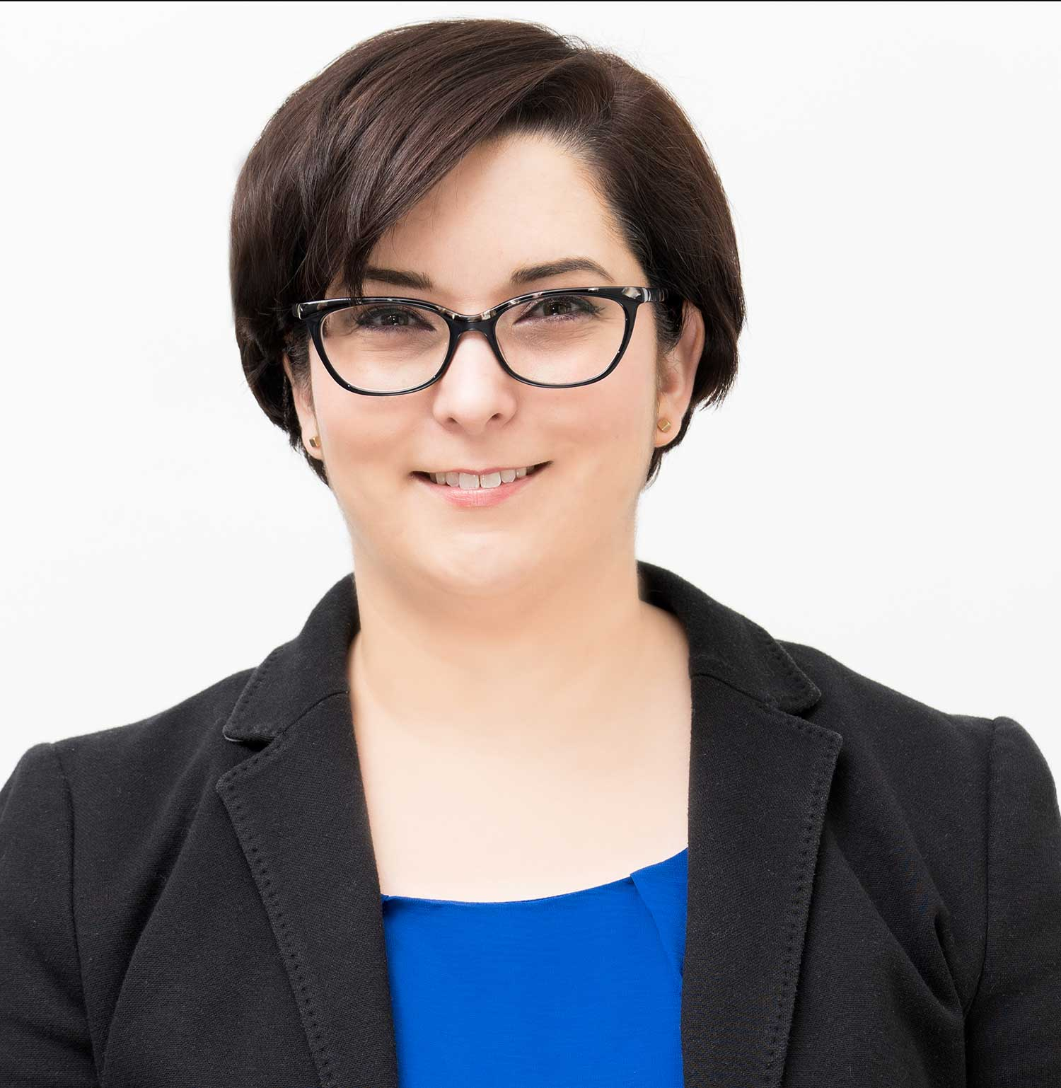 smiling woman with short brown hair and glasses wearing black blazer and blue shirt