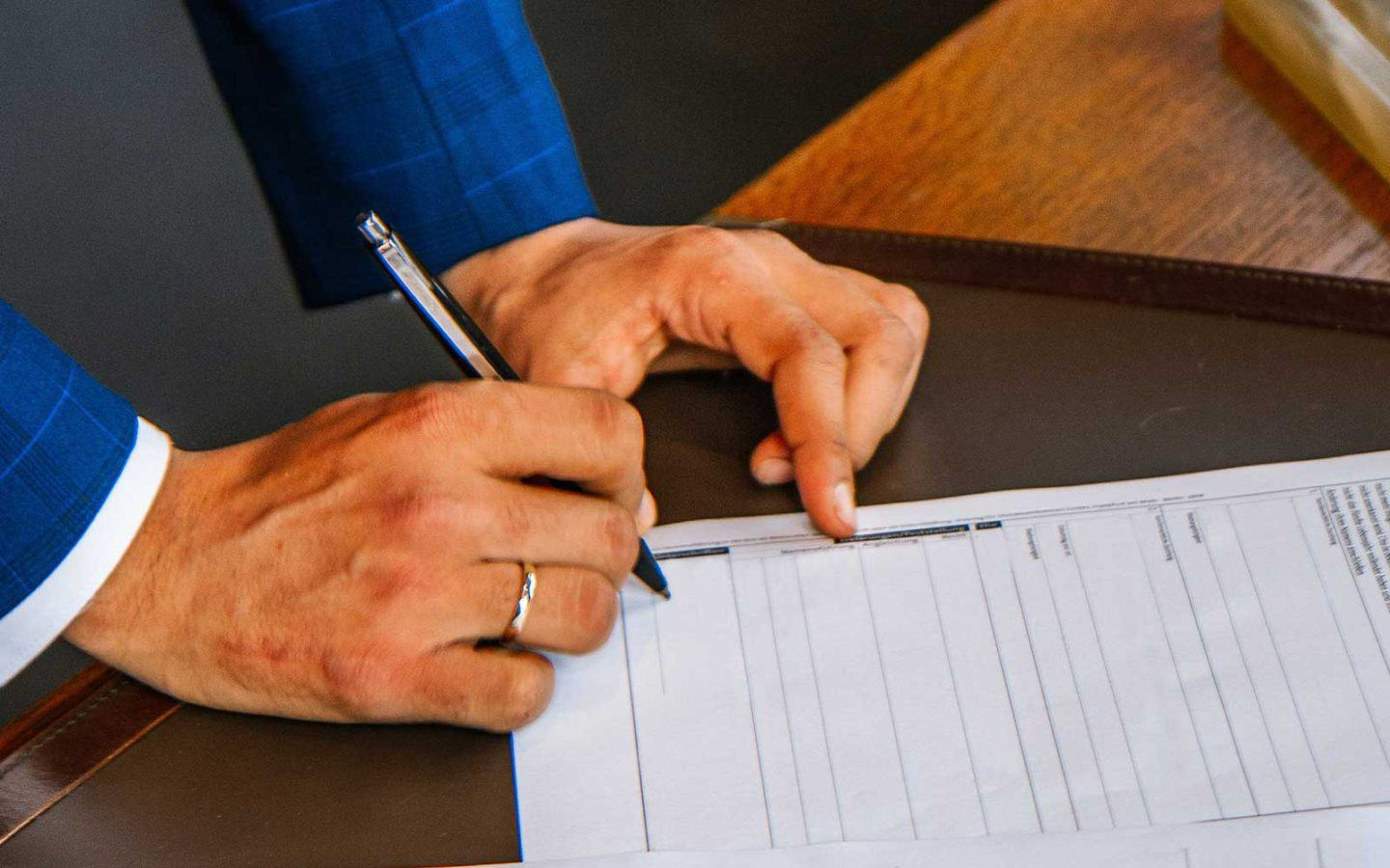 arm of man in blue suit holding pen writing on paper