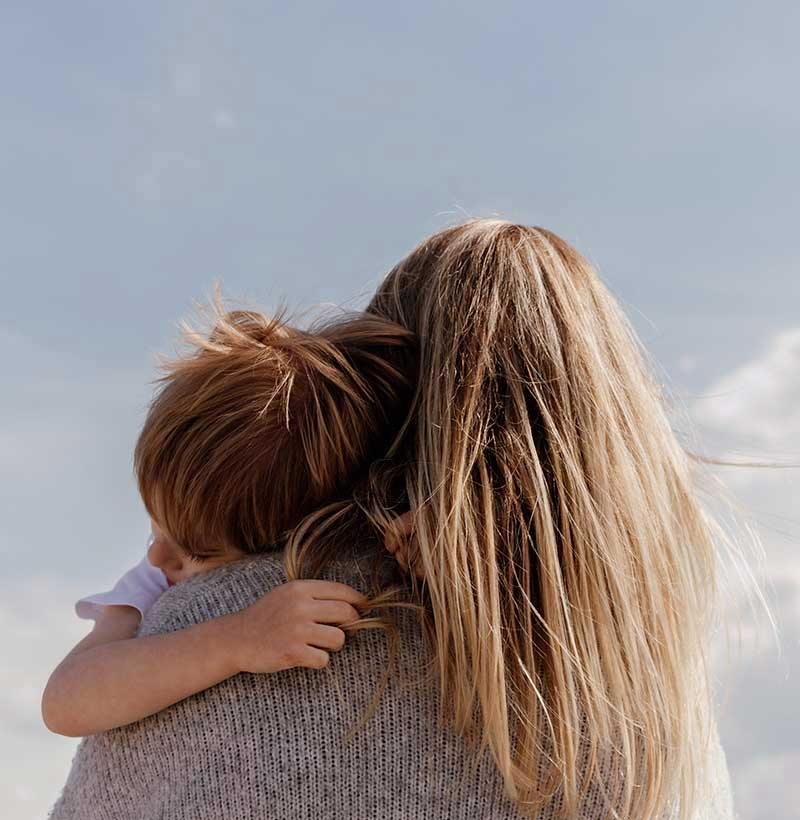 back of woman with long dirty blonde hair holding son